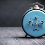 blue alarm clock with sad face